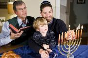 Three generations of a Jewish family light a menorah during Hanukkah