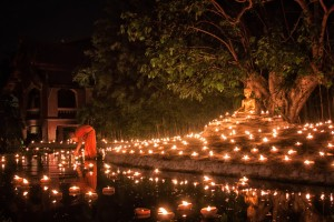 A monk lighting up candles in a pond during Visakha Bucha night in Chiang Mai, Thailand