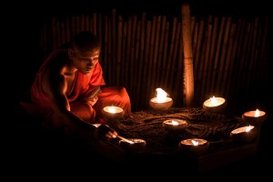 A monk slowly lighting up candles during Asalaha Bucha in Chiang Mai, Thailand