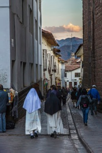 Two nuns walking down a small street in the historic district of Cuzco, Peru