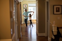father dances with his daughter in their home