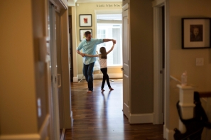 A Father Dances With His Daughter In Their Home
