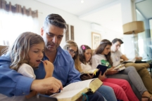 father in Portugal sits with his children in their living room to read from the scriptures together
